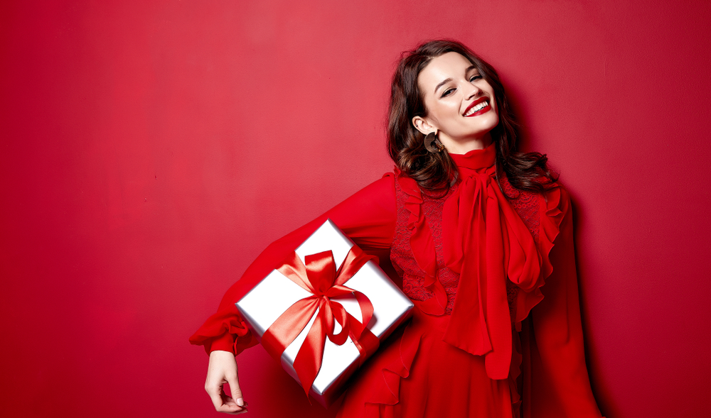 brown haired woman in a red frilled dress and red lipstick standing in front of a red background while holding a white present with a red ribbon in one arm and smiling