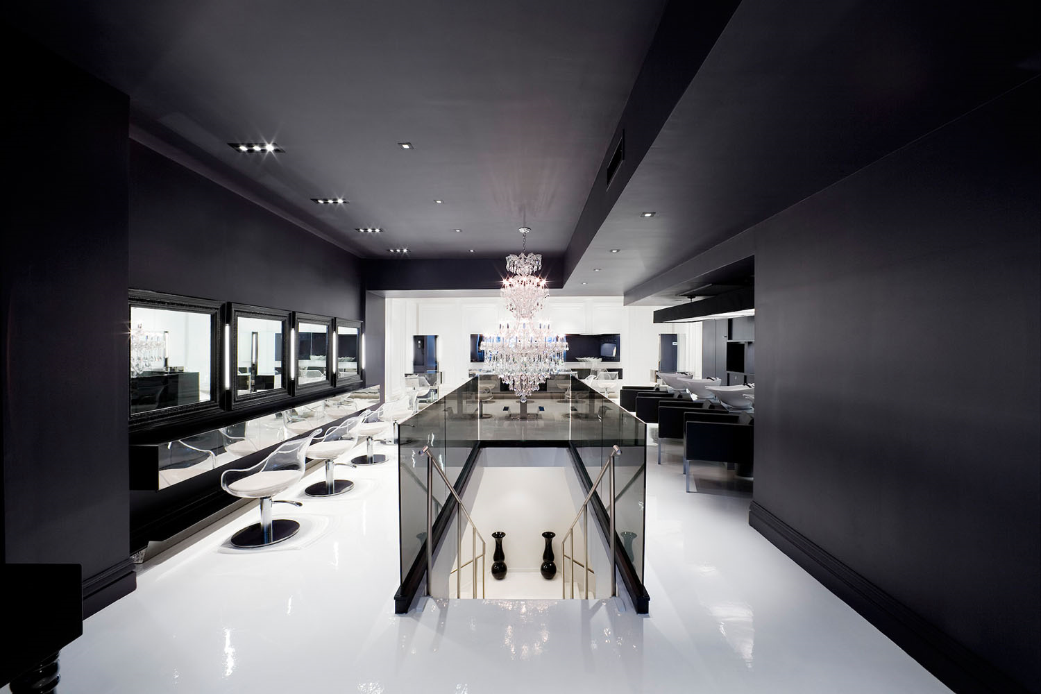 beautiful black and white hair salon with glass furniture and shiny floor and walls