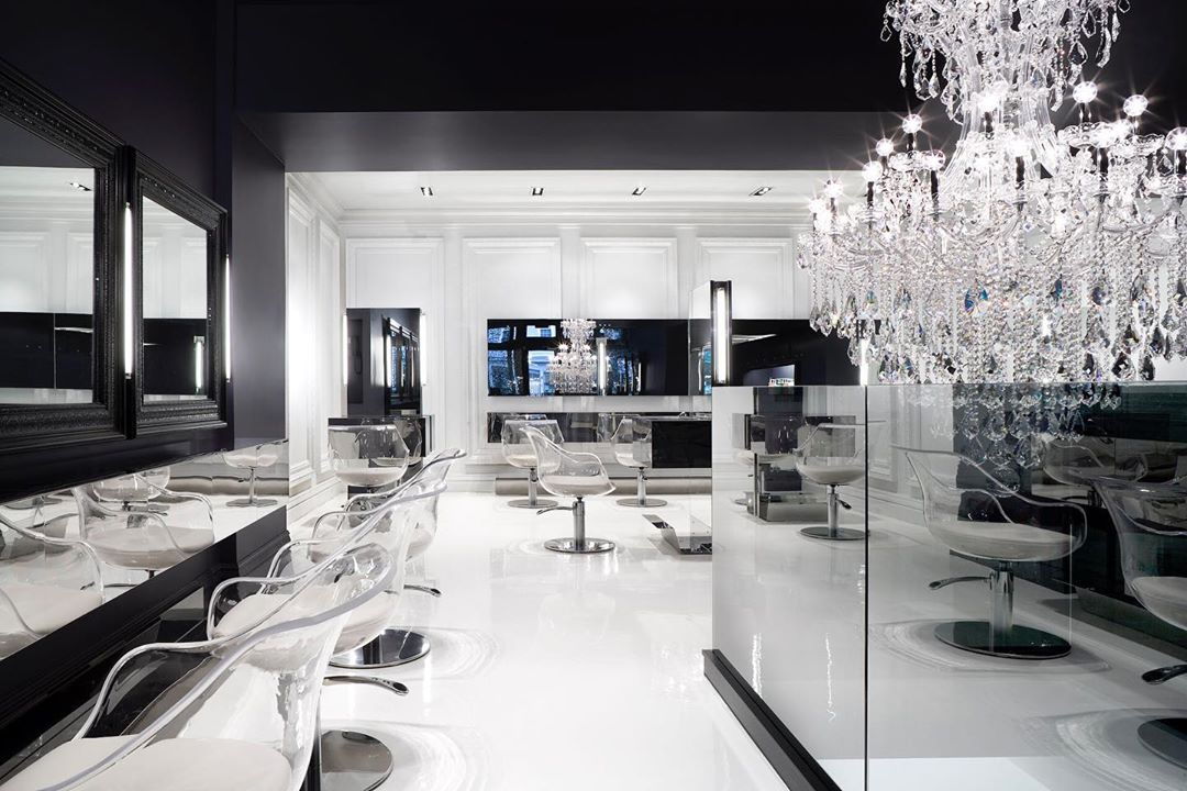beautiful black and white hair salon with luxurious furniture and a chandelier